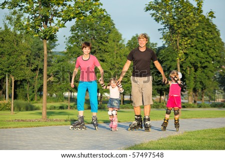 Parents and two daughters skating in a summer park