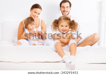 Parents and two kids sit on white bed in morning - stock photo