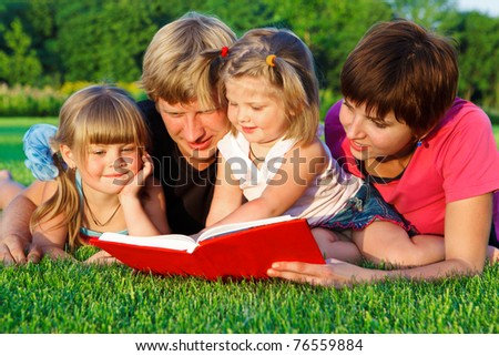 Parents and two preschool daughters reading a book in the backyard - stock photo