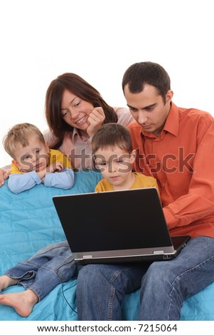 parents and two sons having fun with computer game on the sofa - stock photo
