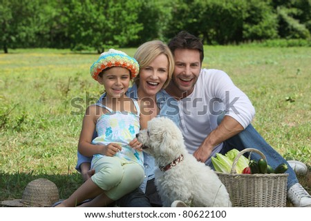 Parents and young daughter with dog and basket of vegetables - stock photo