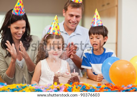 Parents applauding her little daughter who just blew out the candles on birthday cake - stock photo