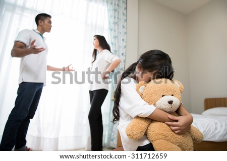 Parents are quarreling daughters feel stressed. She cried, hugging a teddy bear - stock photo