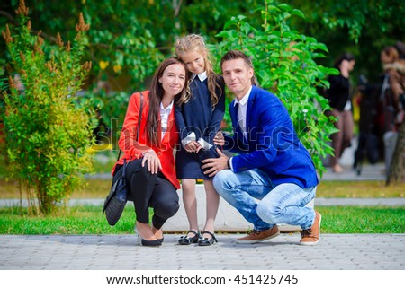 Parents brings theiir little cute daughter to school. Adorable little girl feeling very excited about going back to school - stock photo