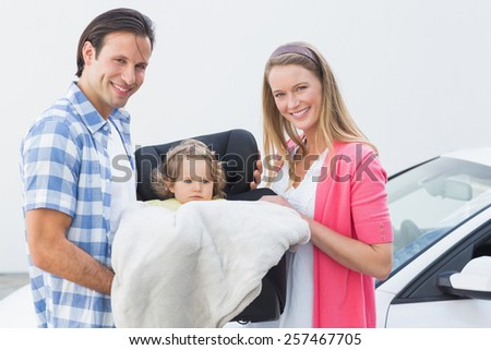 Parents carrying baby in his car seat out of the car - stock photo