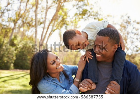 Parents Carrying Son On Shoulders As They Walk In Park
