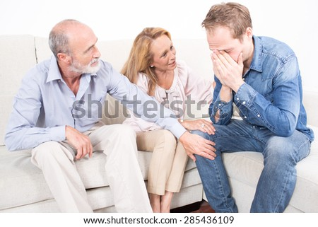 Parents comforting their son - stock photo