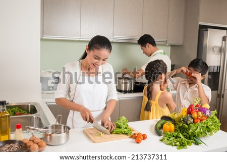 Parents cooking, while their children playing in the kitchen - stock photo