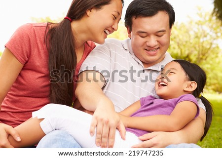 Parents Cuddling Daughter In Park - stock photo