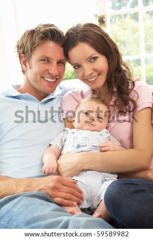 Parents Cuddling Newborn Baby Boy At Home - stock photo
