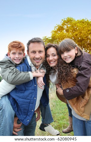 Parents doing piggyback to their children in countryside - stock photo