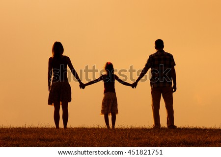 Parents enjoy watching sunset with their daughter.Precious family moments