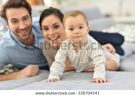 Parents enjoying playing with baby girl - stock photo