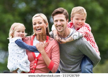 Parents Giving Children Piggybacks In Countryside - stock photo