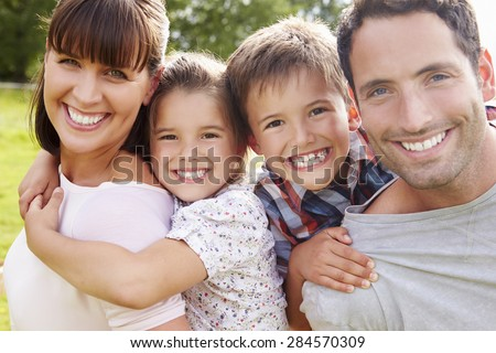 Parents Giving Children Piggybacks Outdoors - stock photo
