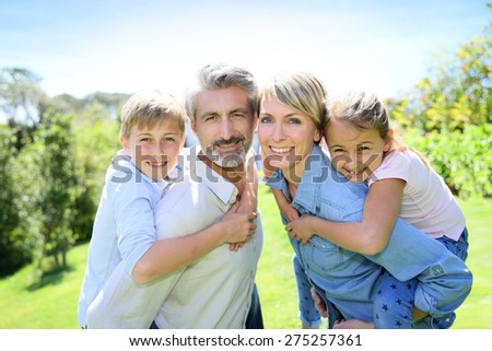 Parents giving piggyback ride to kids in garden - stock photo