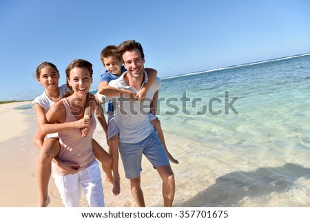 Parents giving piggyback ride to kids on a sandy beach