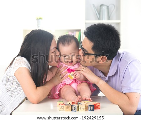 Parents giving their baby daughter a kiss attack. - stock photo