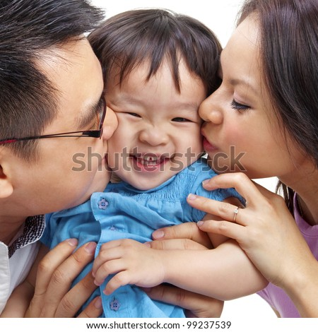 Parents giving their daughter a kiss. - stock photo