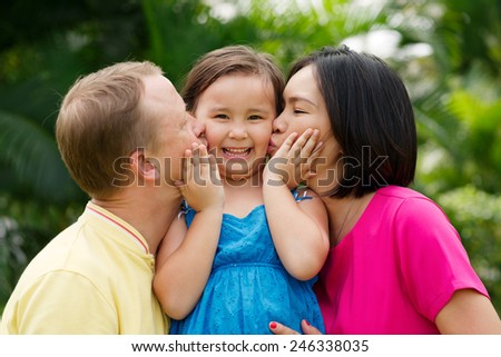 Parents giving their little daughter a kiss