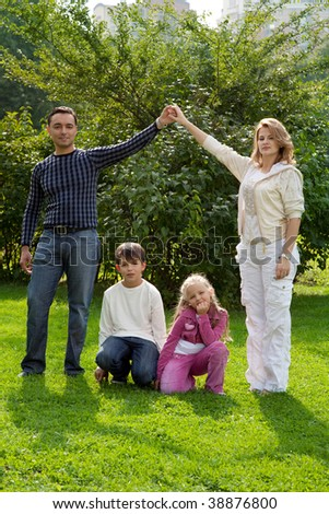 parents hand by hand with children in park, making house, sitting children - stock photo