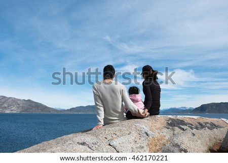 Parents Happy Family Holding hands, sitting on a rock overlooking the turquoise sea. Skies In a happy holiday.