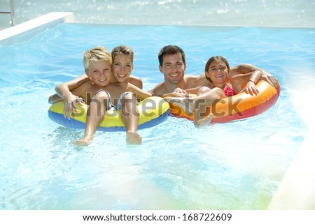 Parents having fun with kids in swimming-pool - stock photo