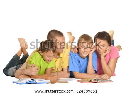 Parents help children do their homework on the floor - stock photo