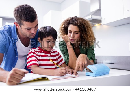 Parents helping son with homework in kitchen