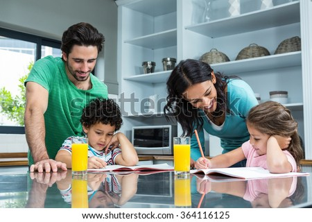 Parents helping their children doing homework in the kitchen - stock photo