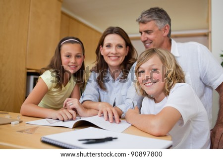Parents helping their children with homework - stock photo