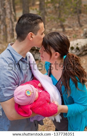 Parents holding baby daughter while being affectionate - stock photo