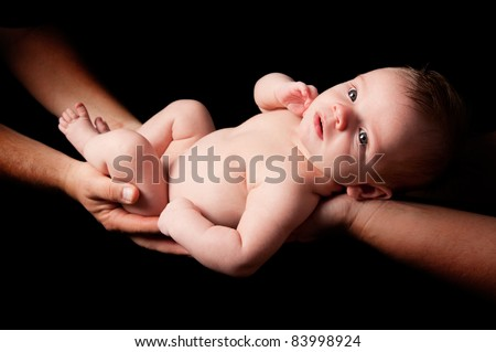 Parents holding baby over black background - stock photo