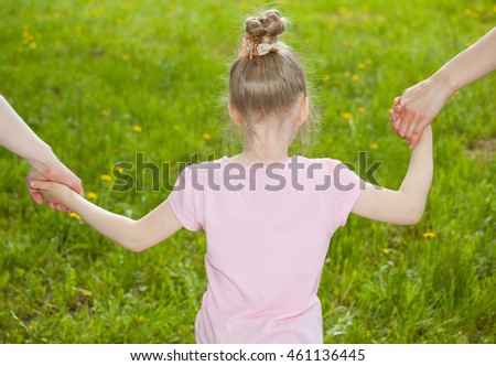 Parents holding daughter's hands, green natural background