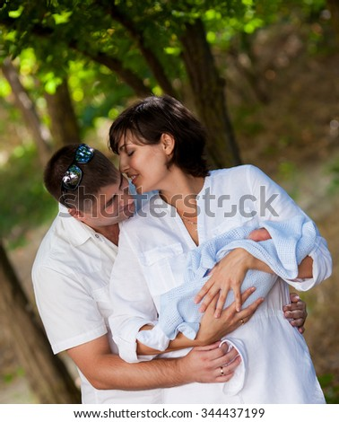 Parents holding newborn baby - stock photo