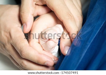 parents holding their baby girl's hand