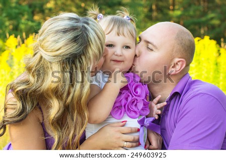 Parents kiss the child on the cheek - stock photo