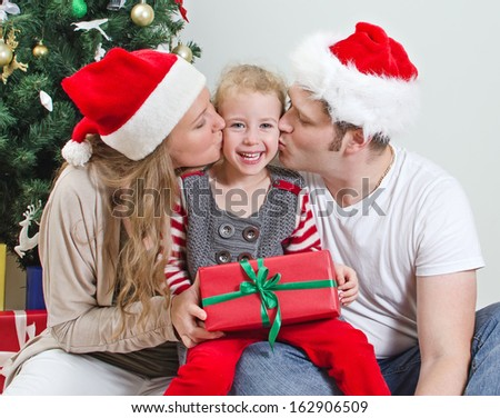 Parents kissing daughter in front of christmas tree. - stock photo