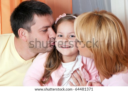 parents kissing daughter portrait looking very happy - stock photo