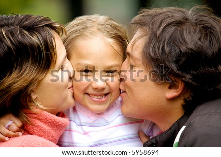 parents kissing daughter portrait looking very happy outdoors - stock photo