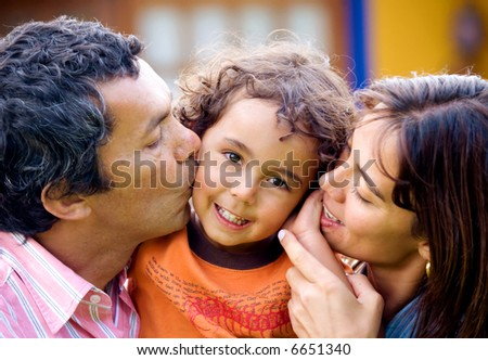 parents kissing son portrait outdoors at home - kid is smiling - stock photo