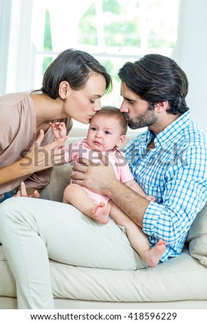 Parents kissing son while sitting on sofa at home