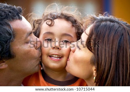 parents kissing their son and smiling - stock photo