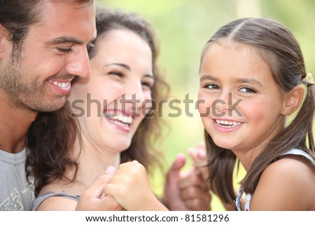 Parents laughing with their daughter - stock photo