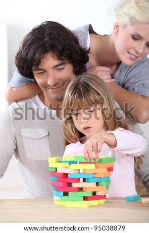 parents looking her daughter playing with blocks