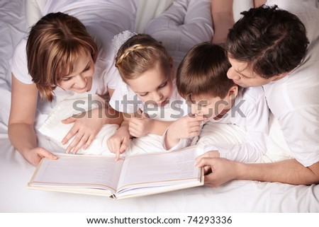 Parents of children reading a book - stock photo