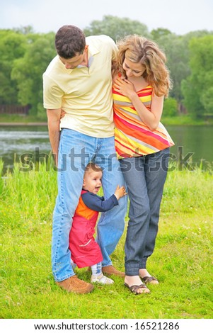 Parents on  meadow at water and child between legs