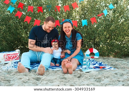 parents playing with their child sitting on the beach - stock photo