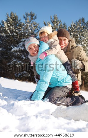 Parents playing with their toddler daughter in a winter wood - stock photo