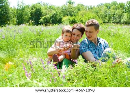 Parents playing with toddler in the meadow - stock photo